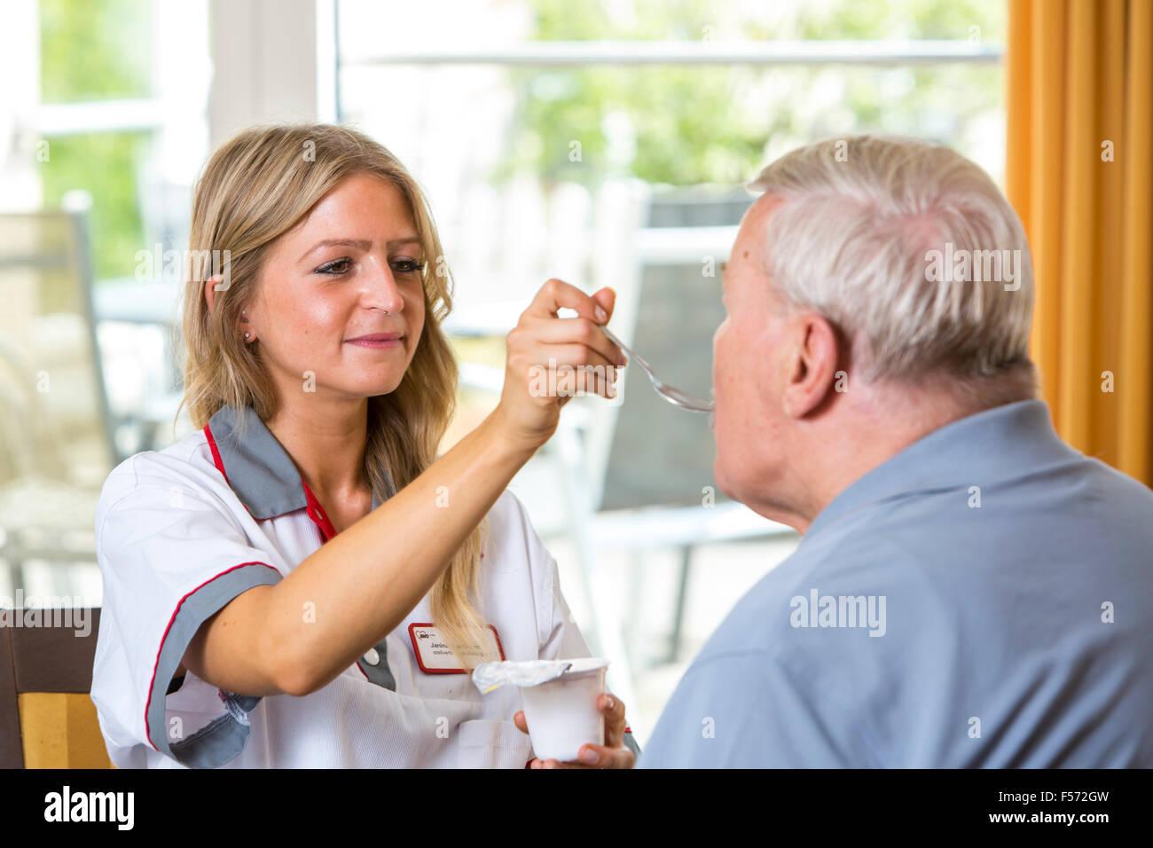 Pflege im Altenheim, Pflege im Altenheim, Altenpflegerin betreut ältern Mann, Hilfe beim essen Stock Photo