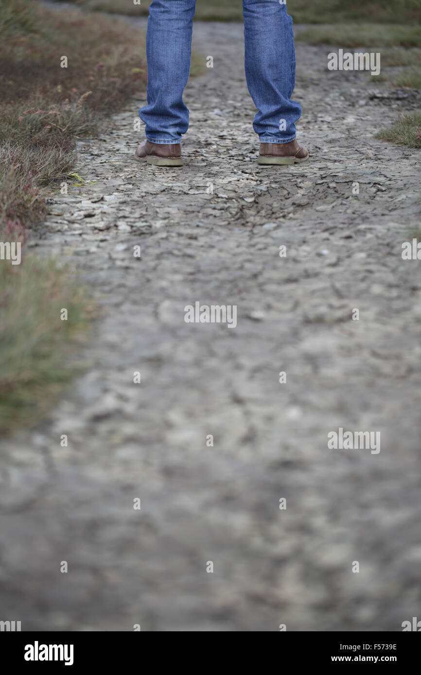 Man's legs standing on cracked ground - Stock Image