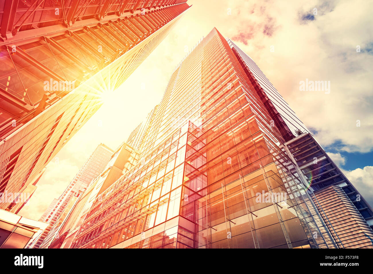 Vintage toned sunset over skyscrapers, modern business background with flare effect. - Stock Image