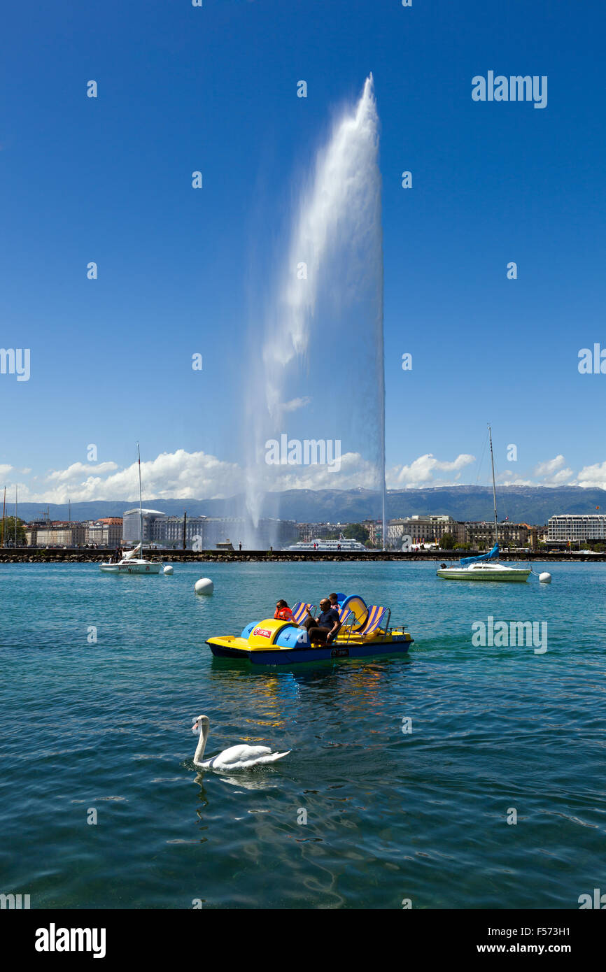 A swan and a pedalo are swimming in front of the Jet d´eau, a 140m high water fountain which is a famous landmark - Stock Image
