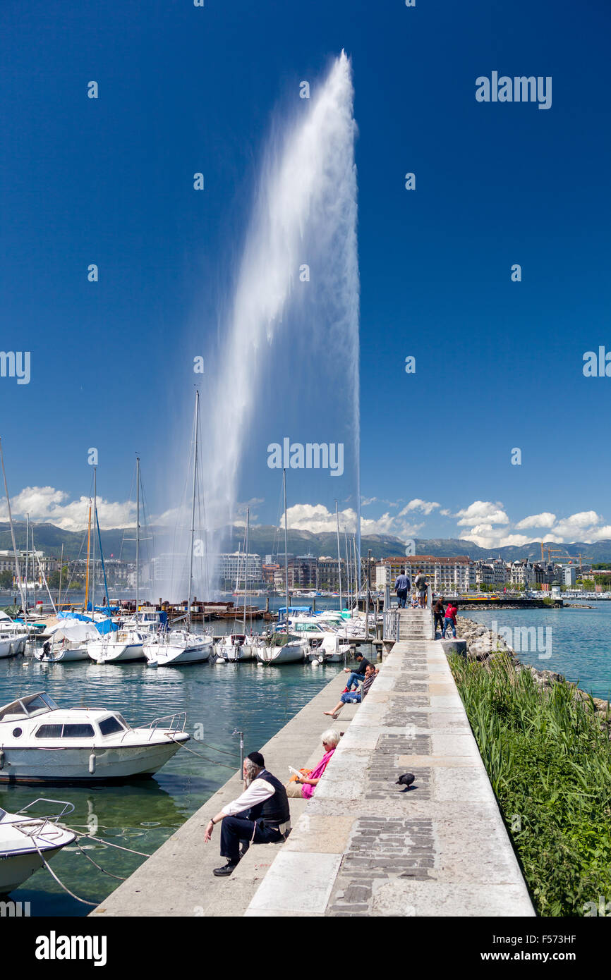 Multicultural people sitting in the sun in front of Jet d´eau, a 140m high water fountain which is a famous - Stock Image