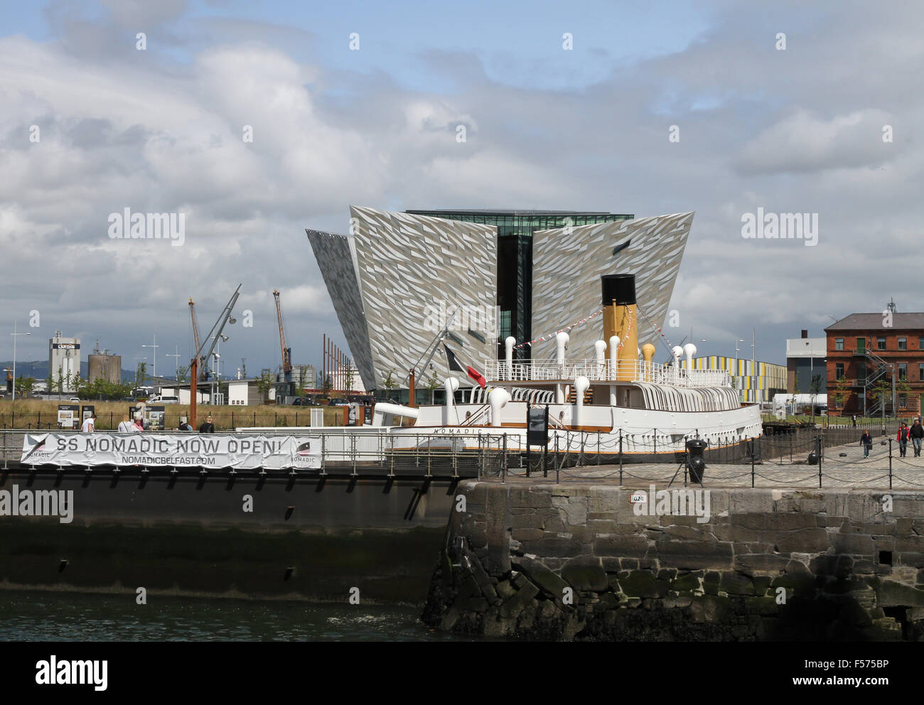The SS Nomadic in Hamilton Dock, Belfast with The Titanic Visitors' Centre in the background. - Stock Image