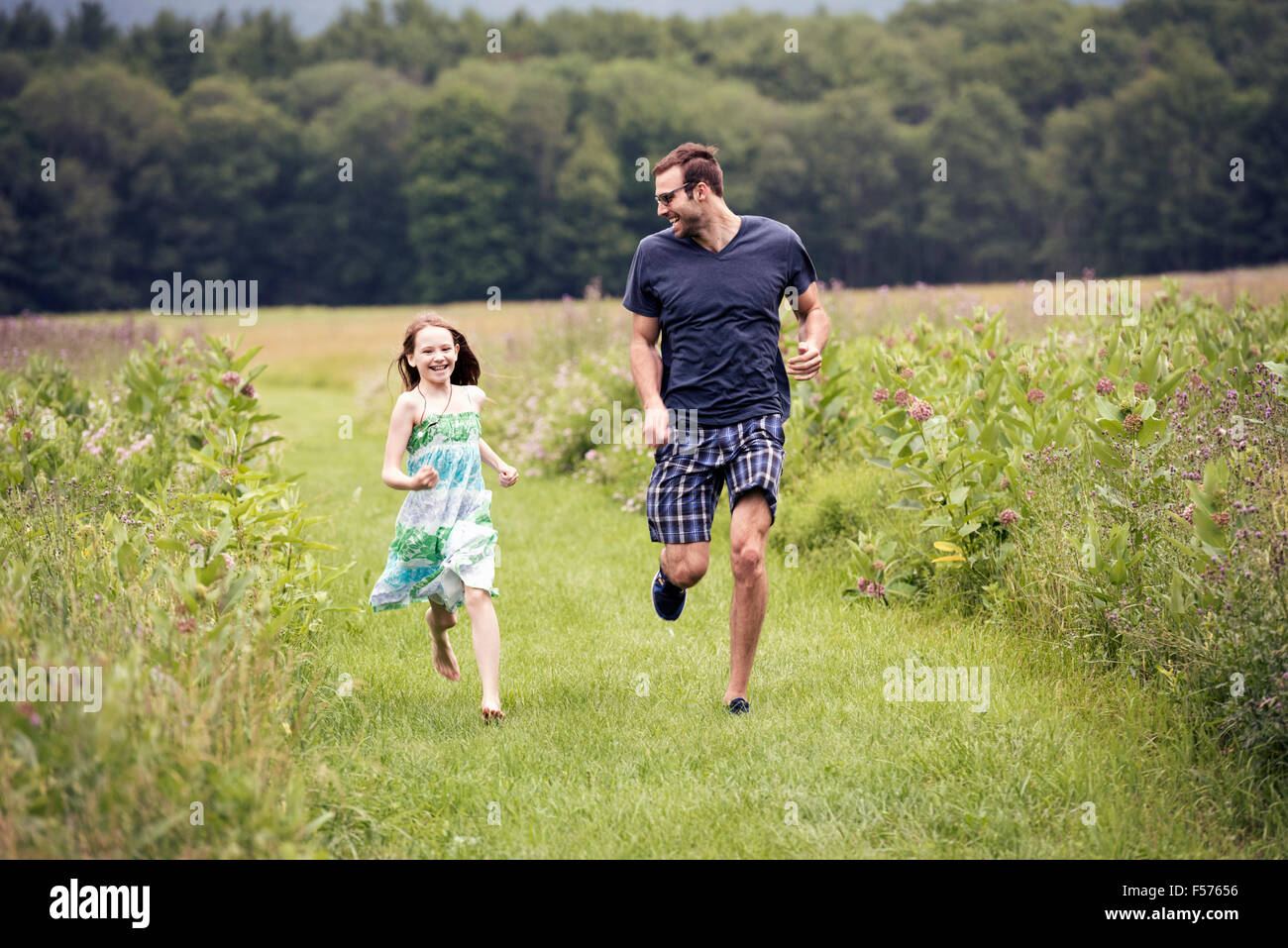 A man and a young child running through a wildflower meadow. - Stock Image