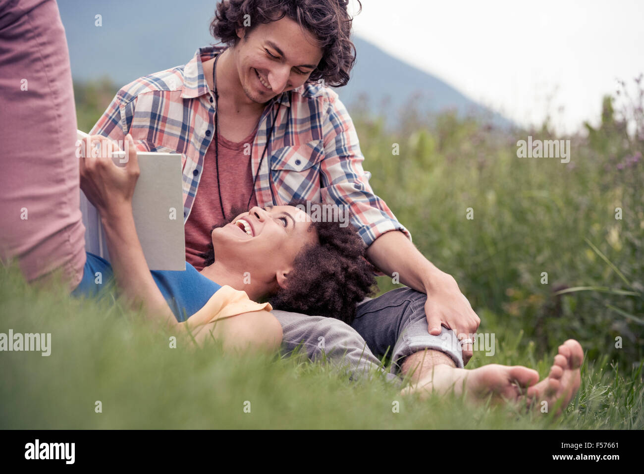 A couple, a woman with an open book looking up at a man smiling at him. - Stock Image
