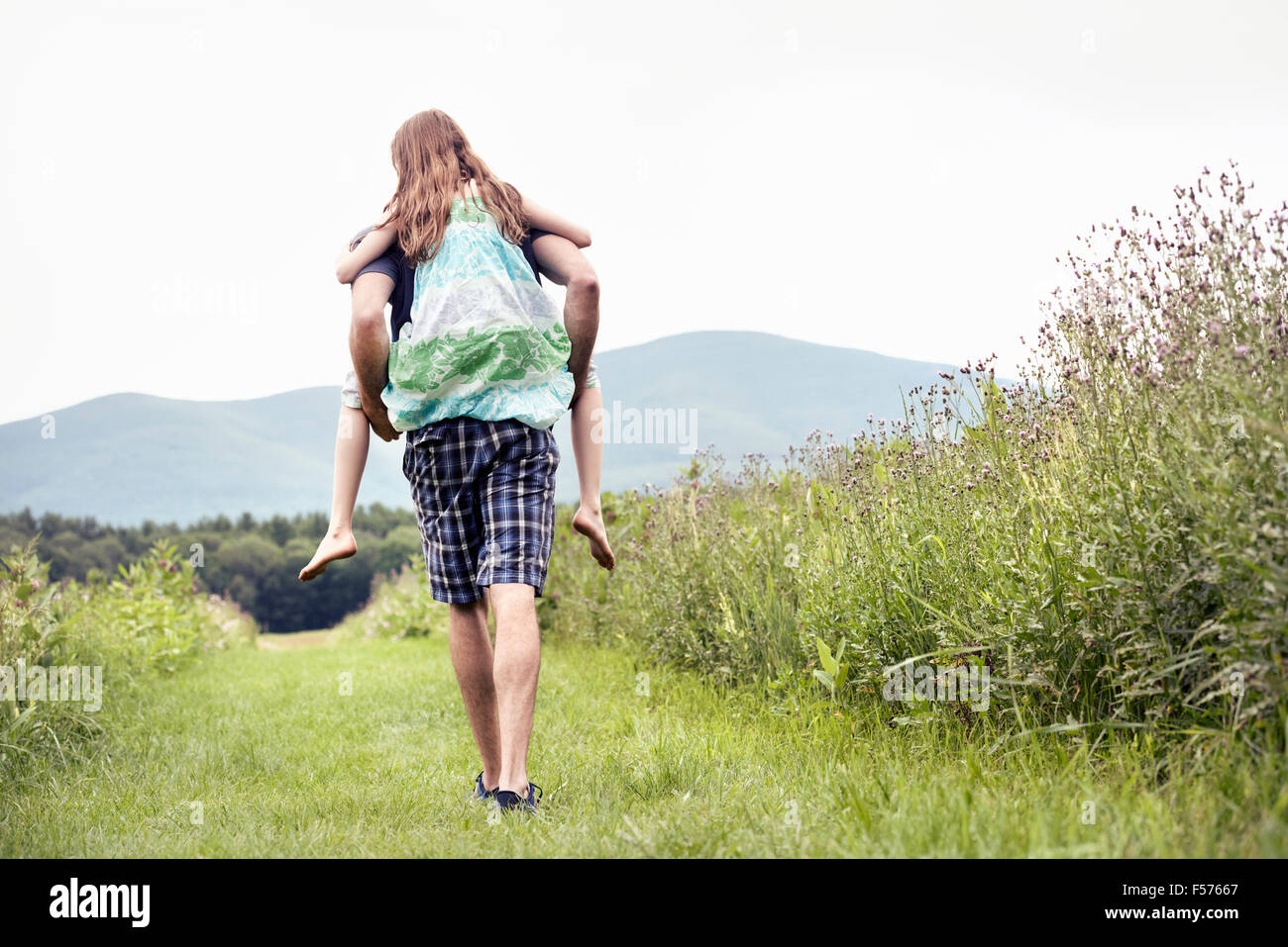 A man giving a young child a piggyback in a meadow. - Stock Image
