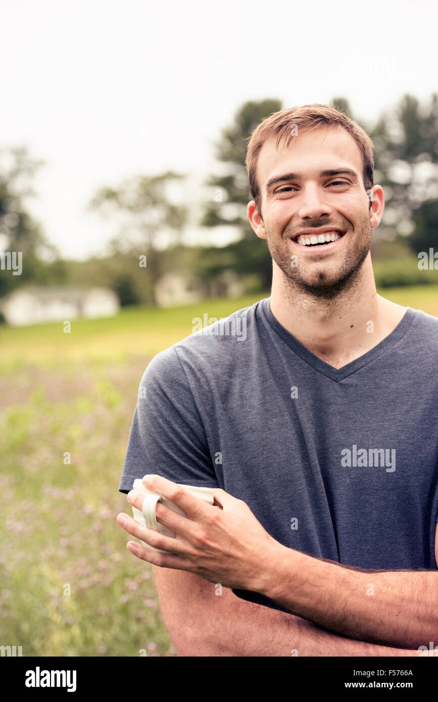 A young man holding a coffee cup standing in a field by a lake. Stock Photo