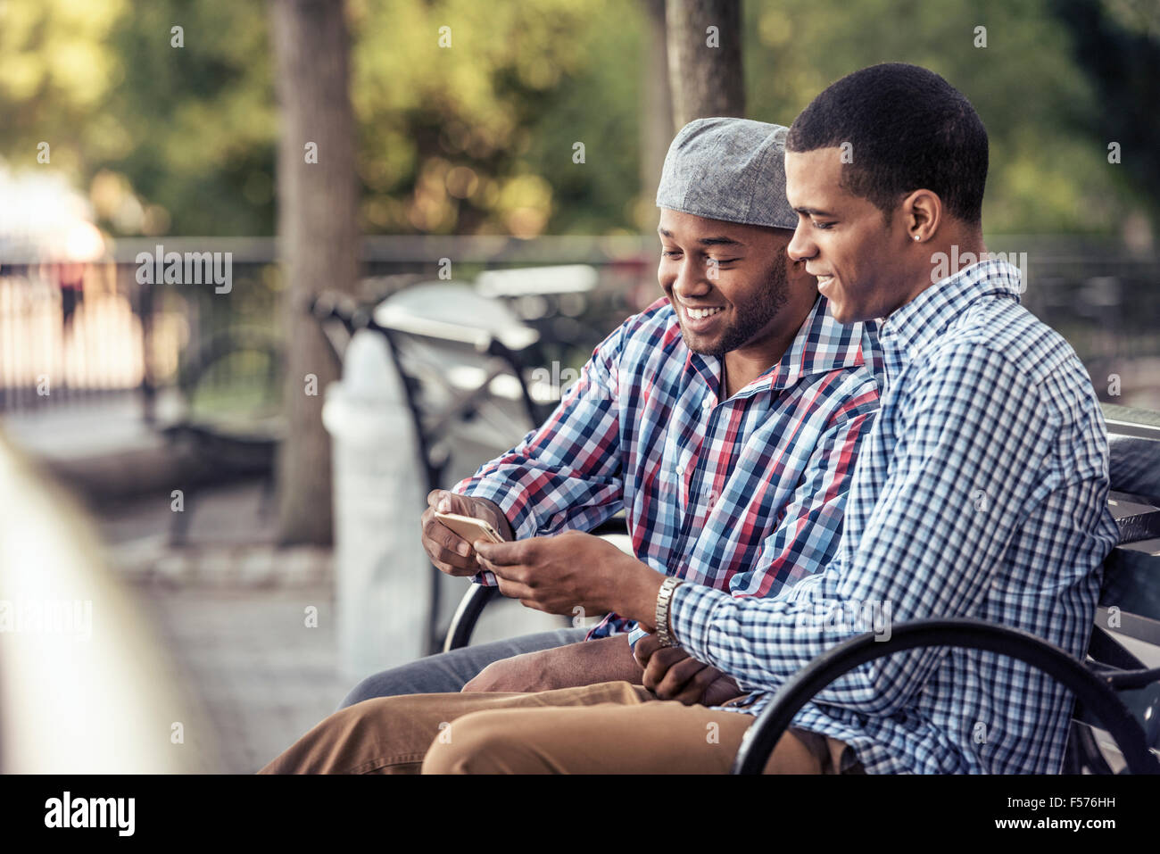 Two men sitting in a park, looking at a smart phone Stock Photo