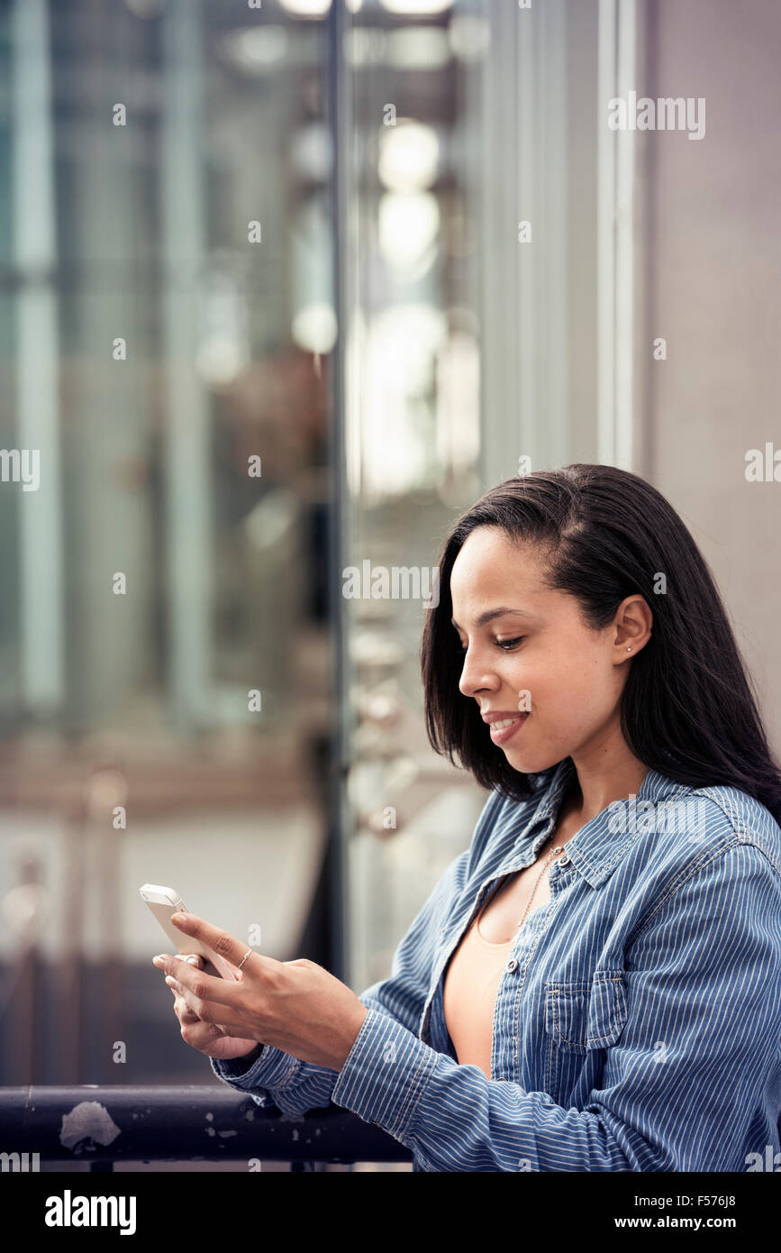 A young woman checking her cell phone on a city street - Stock Image