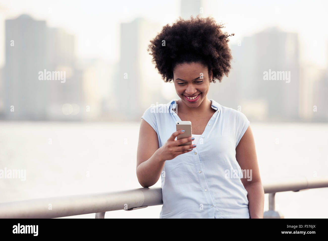 A woman leaning on a waterfront rail checking her cell phone - Stock Image