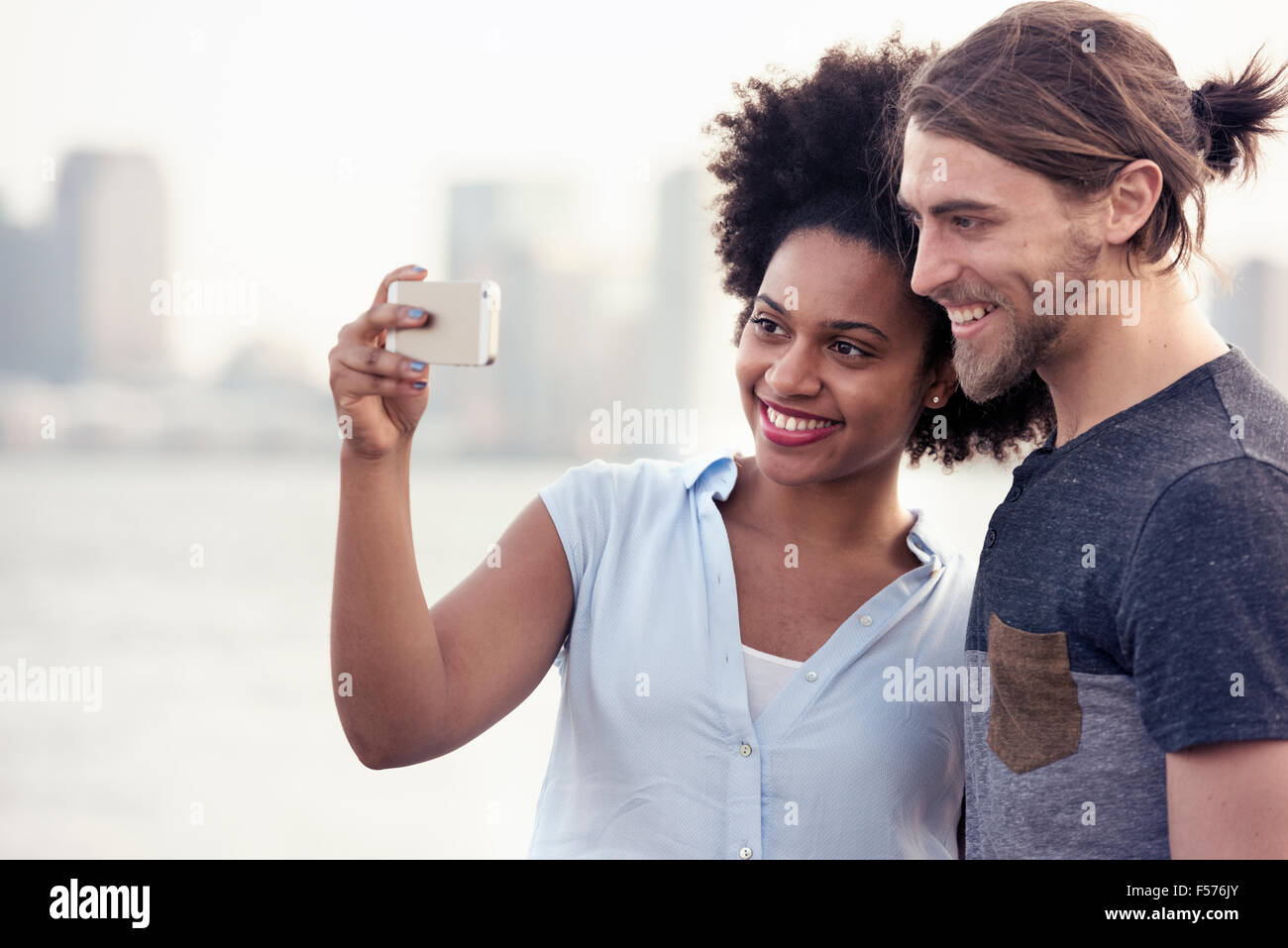 A couple, man and woman taking a selfie by the waterfront in a city - Stock Image