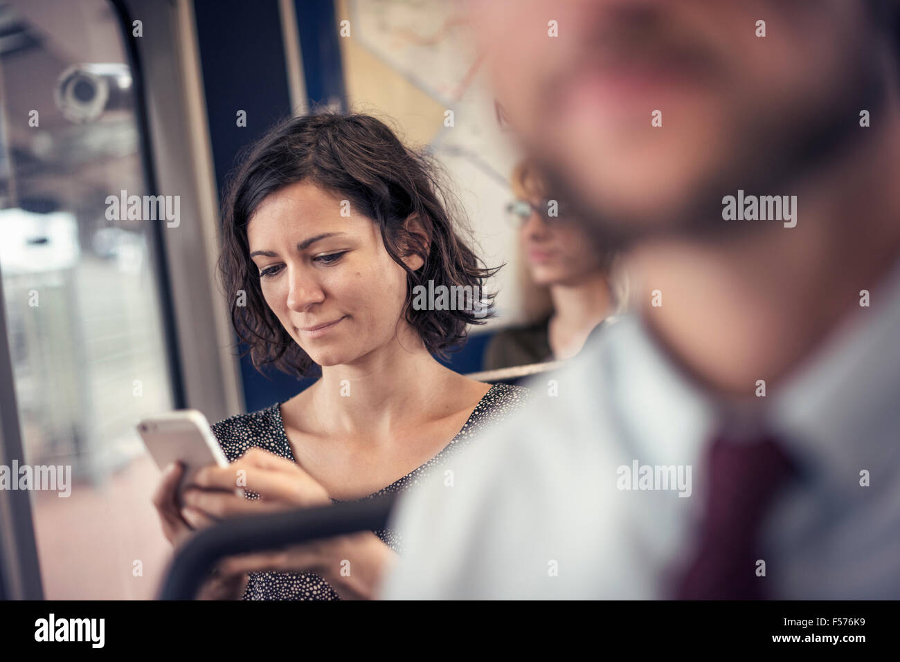 A woman on a bus looking down at her cell phone - Stock Image