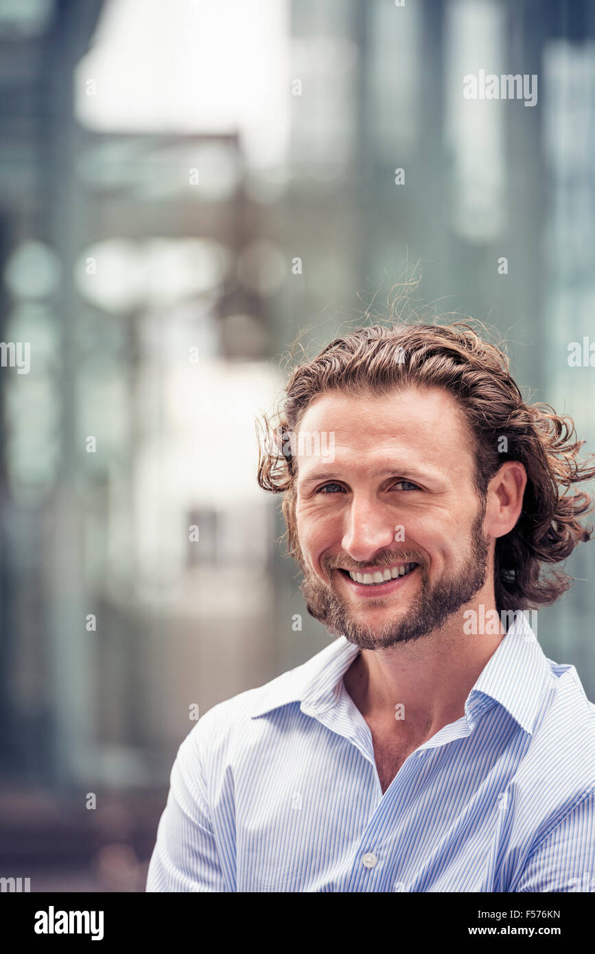 A man with curly hair and a beard on a city street. - Stock Image