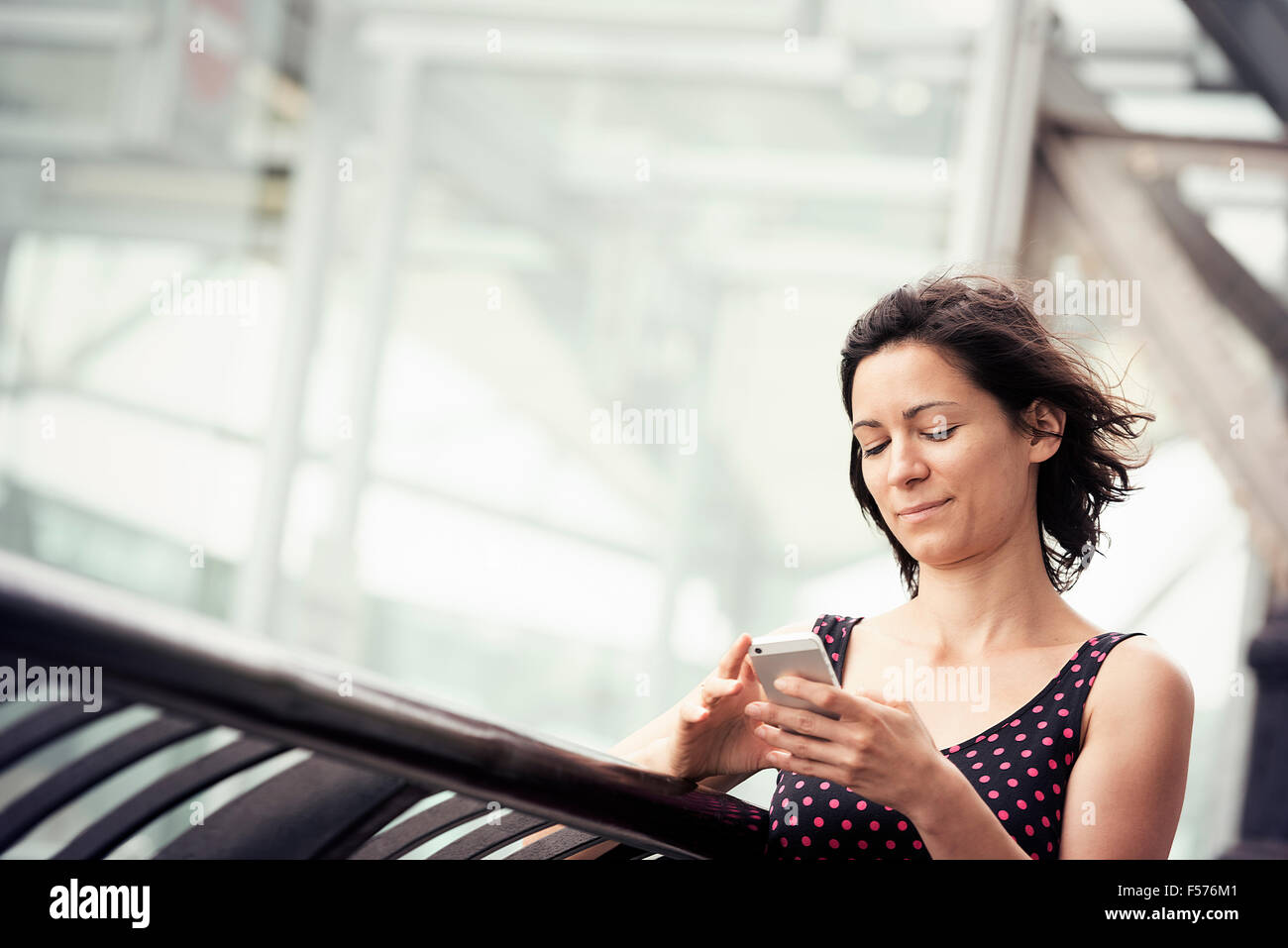 A woman standing outside a building checking her cell phone. - Stock Image