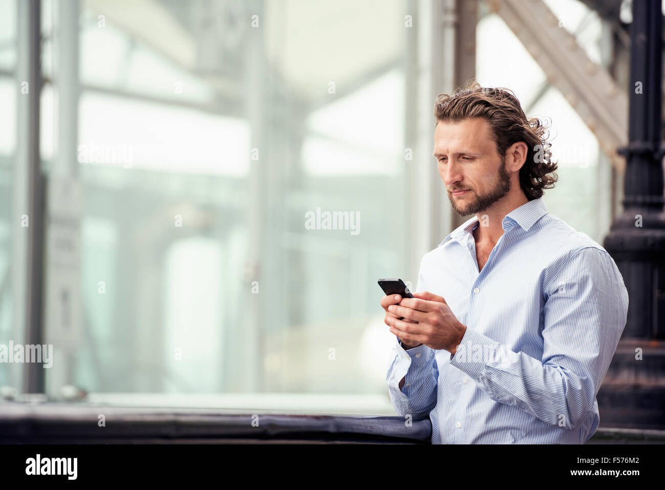 A man standing outdoors on the street, checking his cell phone. - Stock Image