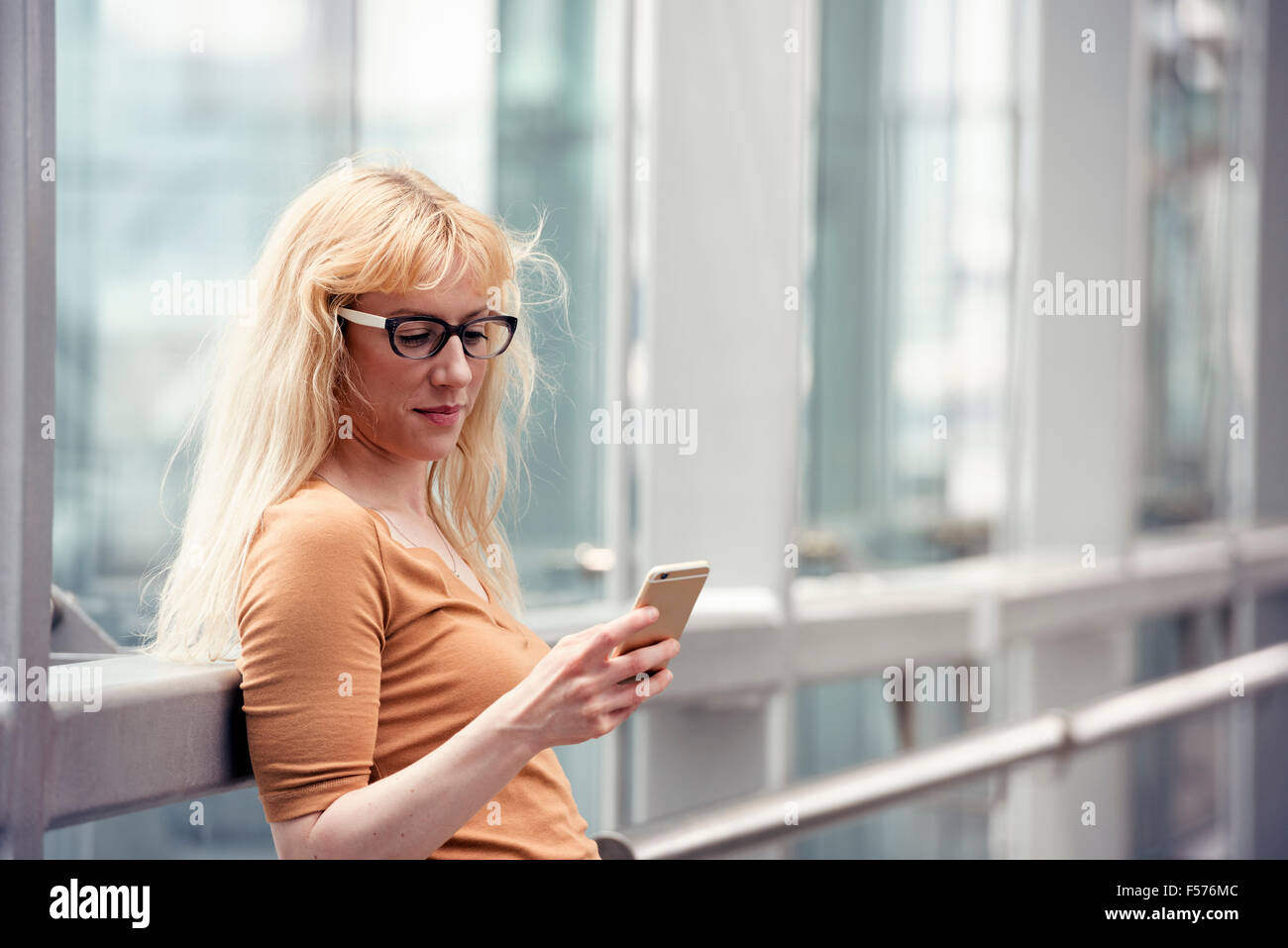 A woman standing outdoors checking her cell phone. - Stock Image