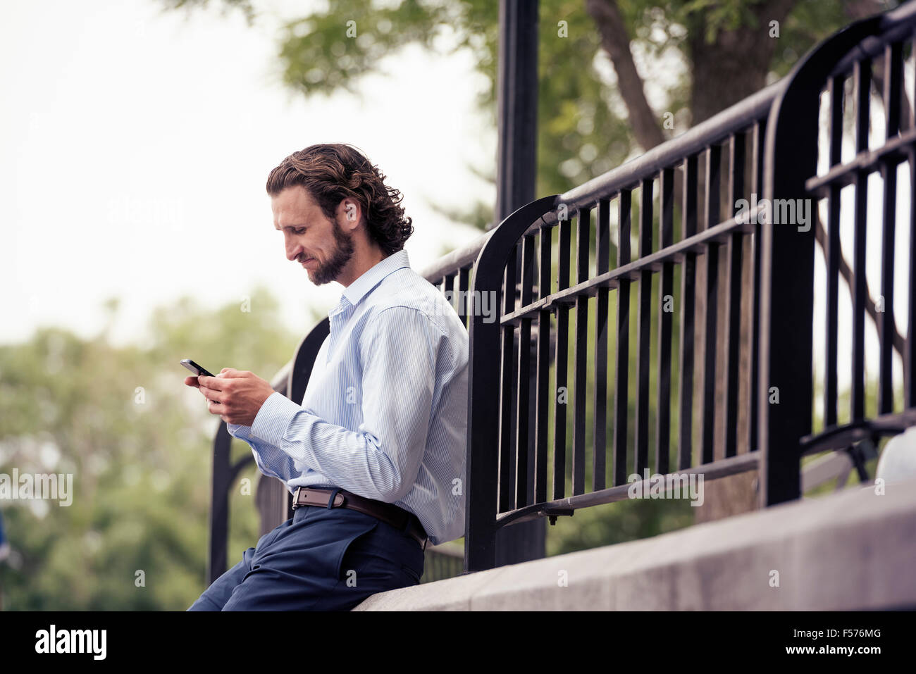 A man pausing on the street, sitting on a step checking his cell phone. - Stock Image
