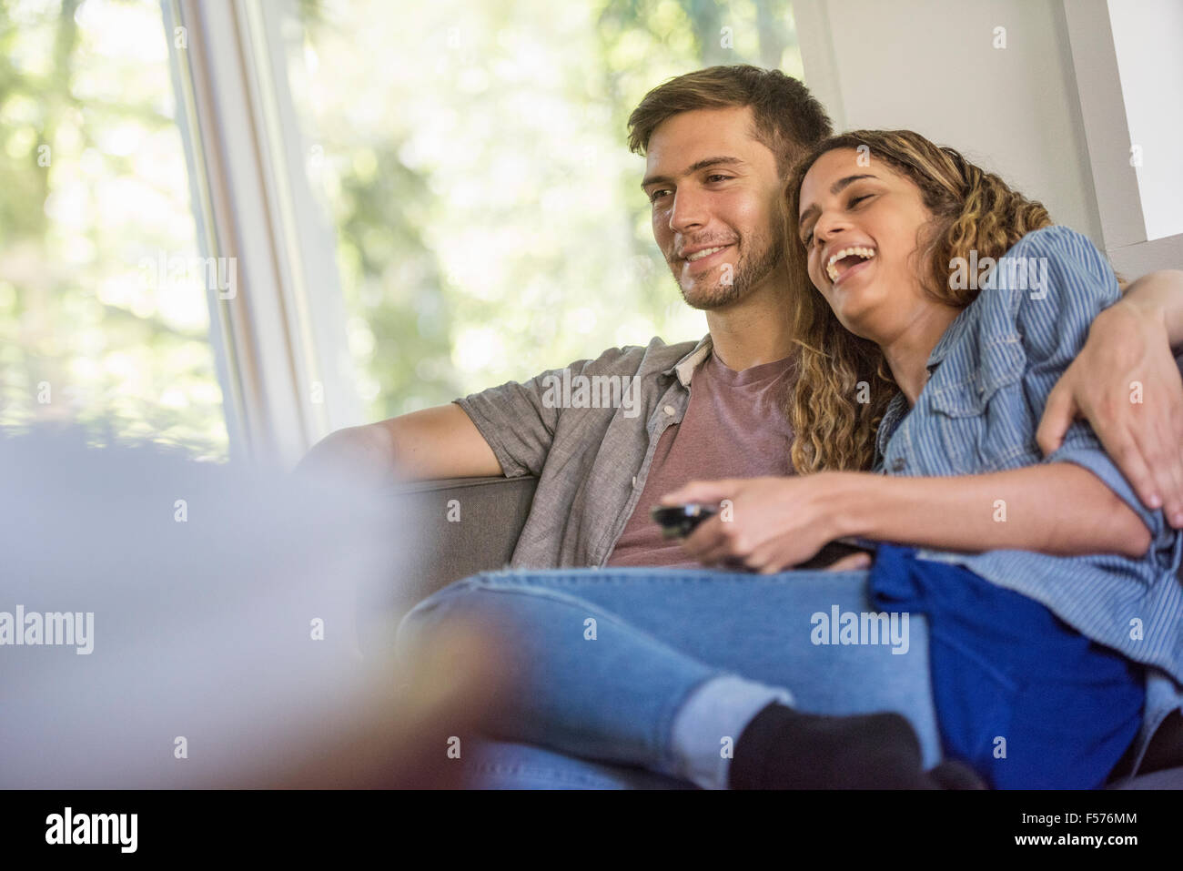 A couple, a man and woman sitting side by side laughing, watching a screen. - Stock Image