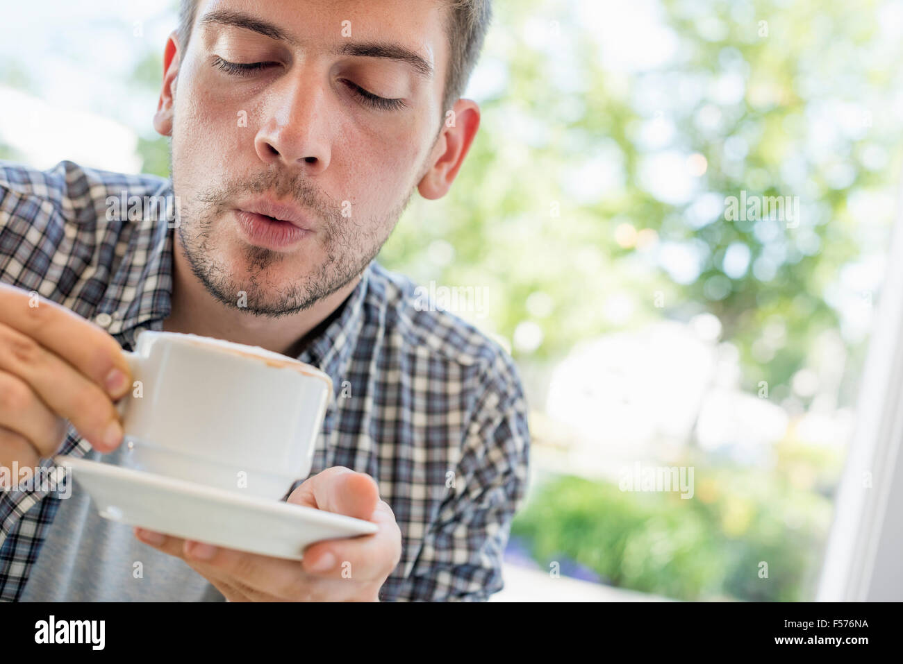 A man blowing on the surface of his hot coffee. - Stock Image