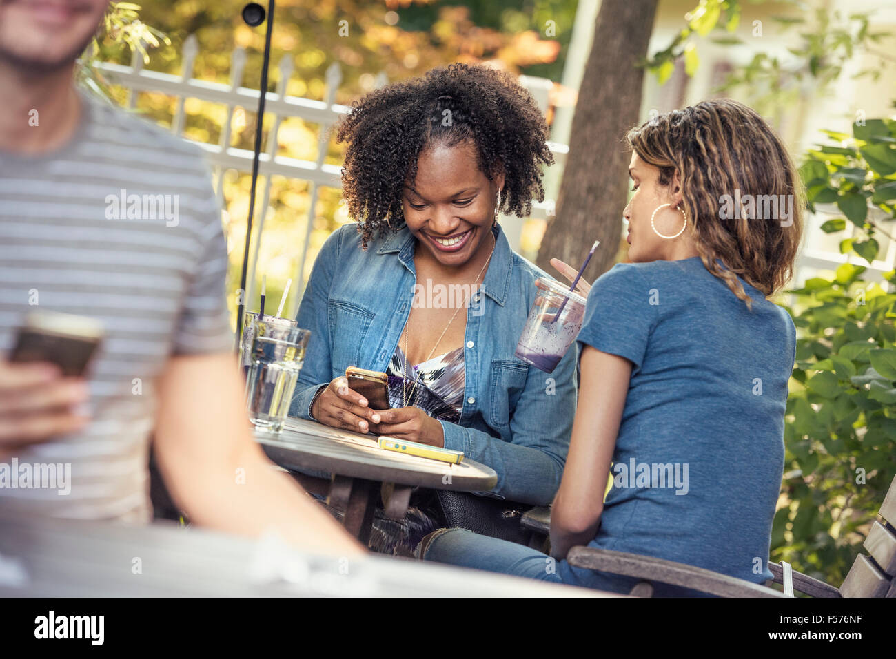 Three people in a cafe diner, two checking their smart phones, - Stock Image