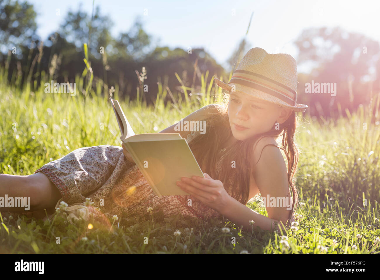 A young girl in a straw hat lying on the grass reading a book. - Stock Image