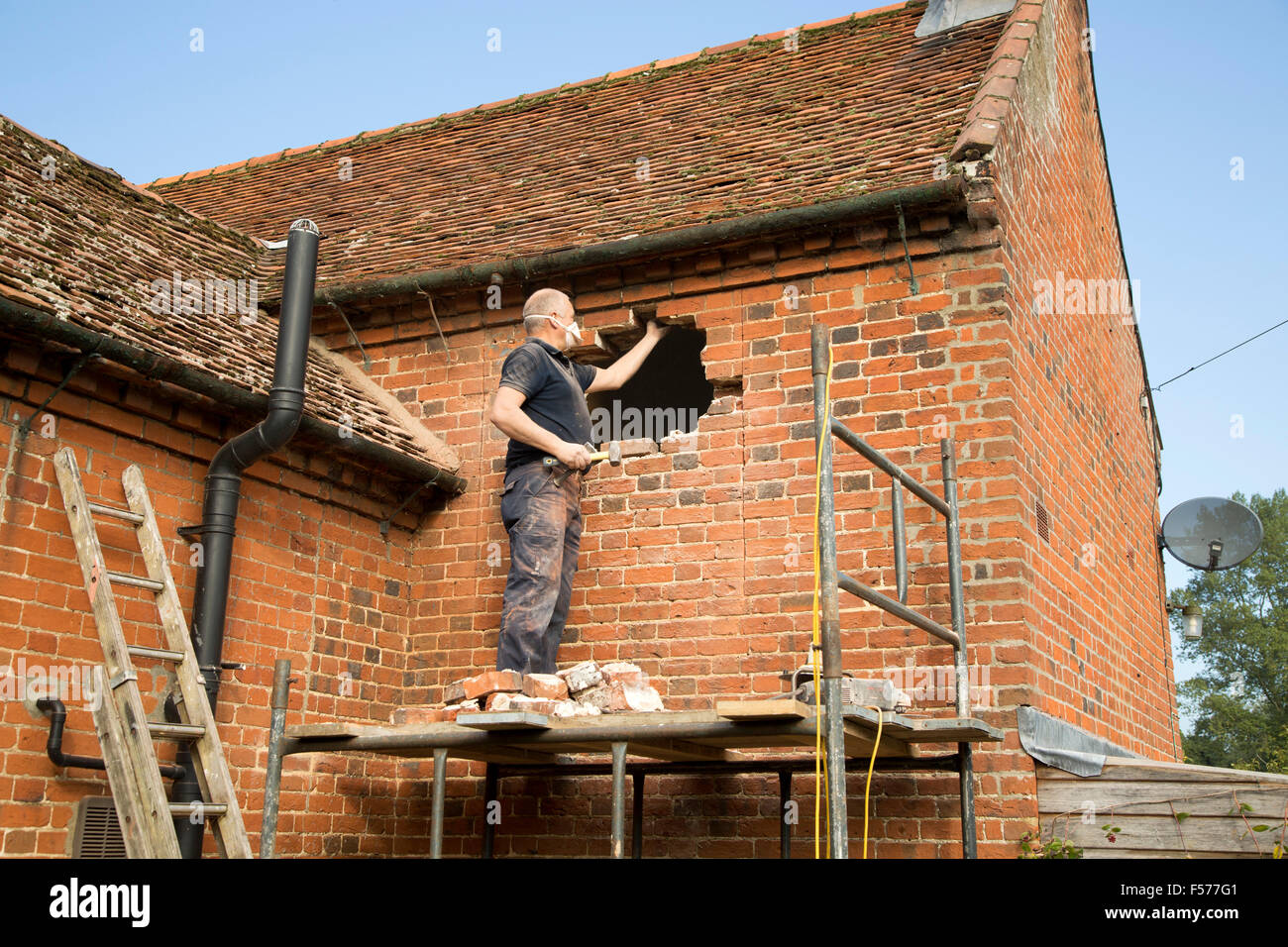 Builder removing red bricks to make window space, Suffolk, England, UK - Stock Image