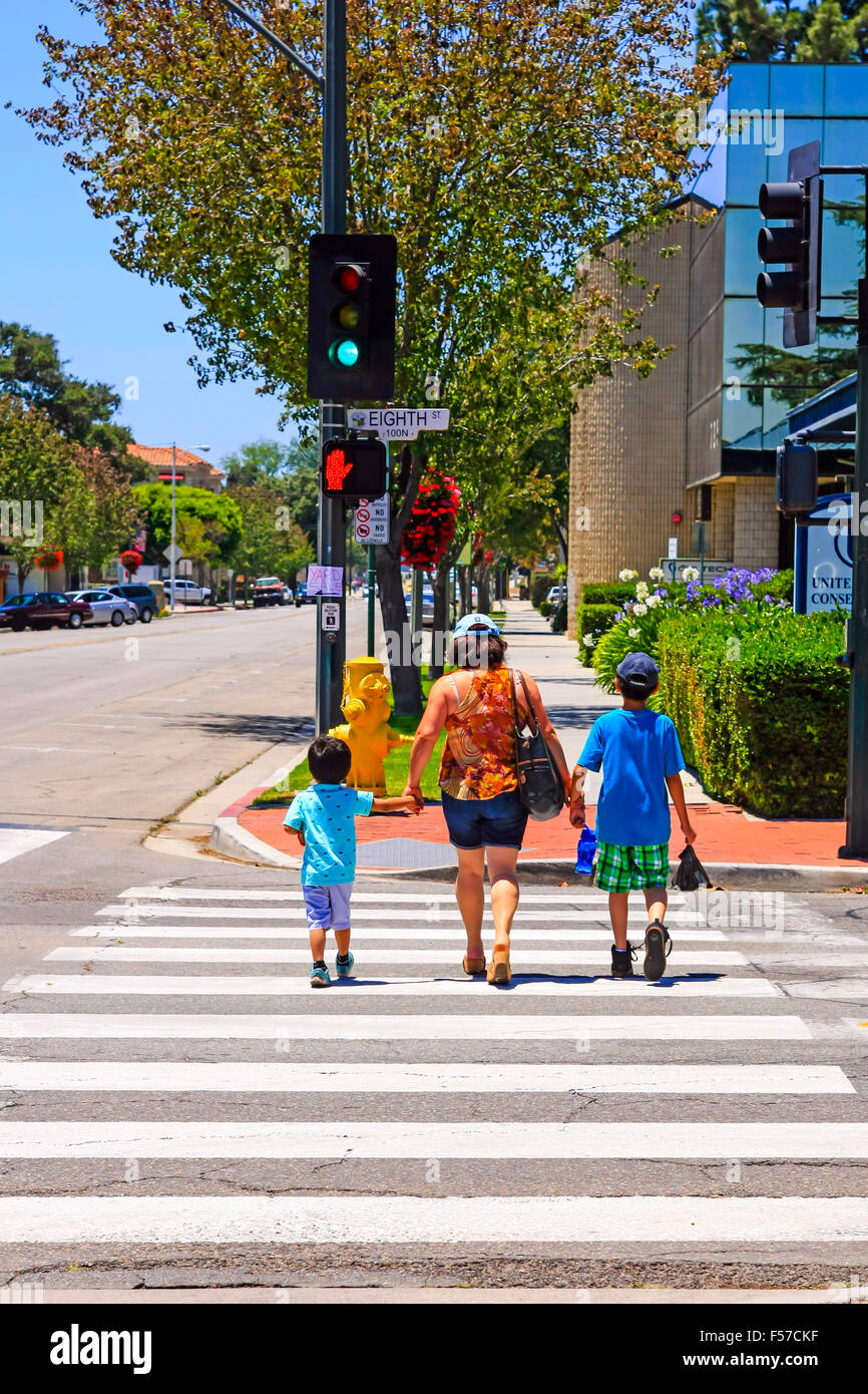 A mother holds the hands of her two children as she crosses a road on the pedestrian walkway in downtown Santa Paula - Stock Image