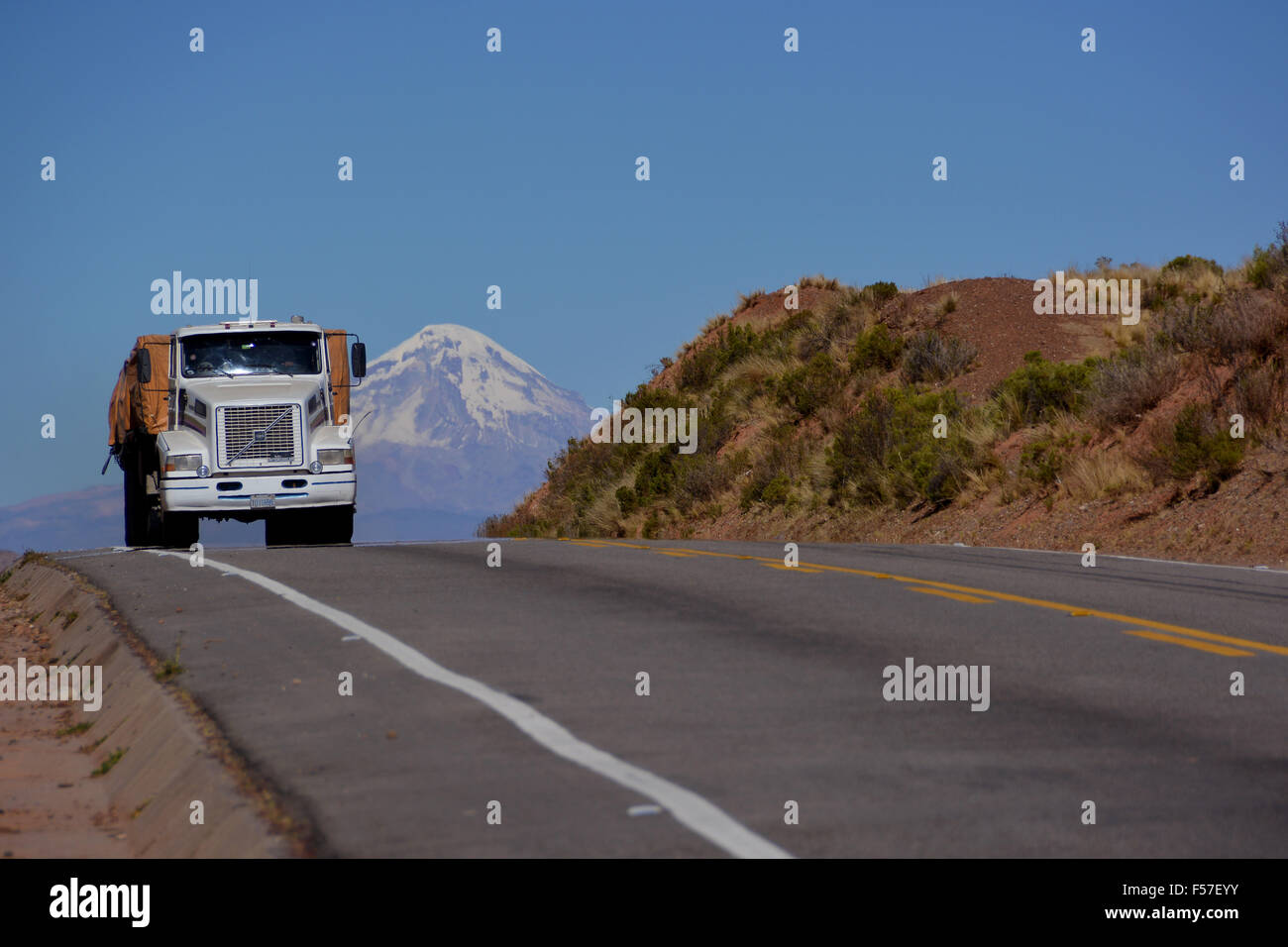 Truck on the road in front of the Sajama volcano, Altiplano, border to Bolivia, Chile - Stock Image