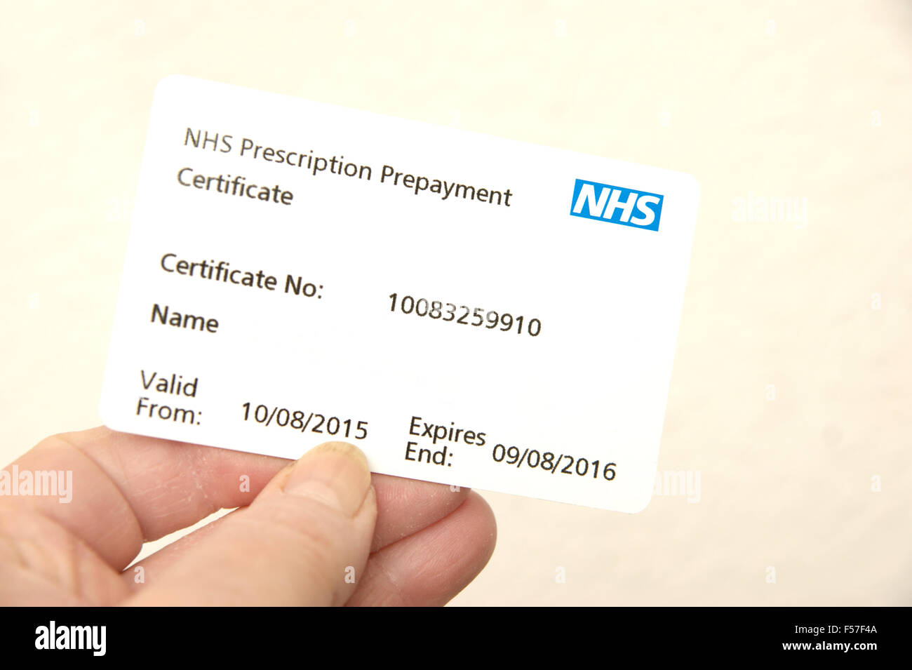 Woman holding an NHS prescription prepayment certificate (useful when lots of medication is taken eg 2 or more scripts - Stock Image