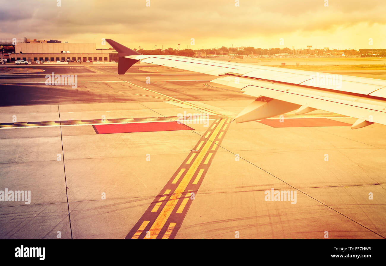 Vintage toned plane wing above runway at sunset, travel concept. Stock Photo