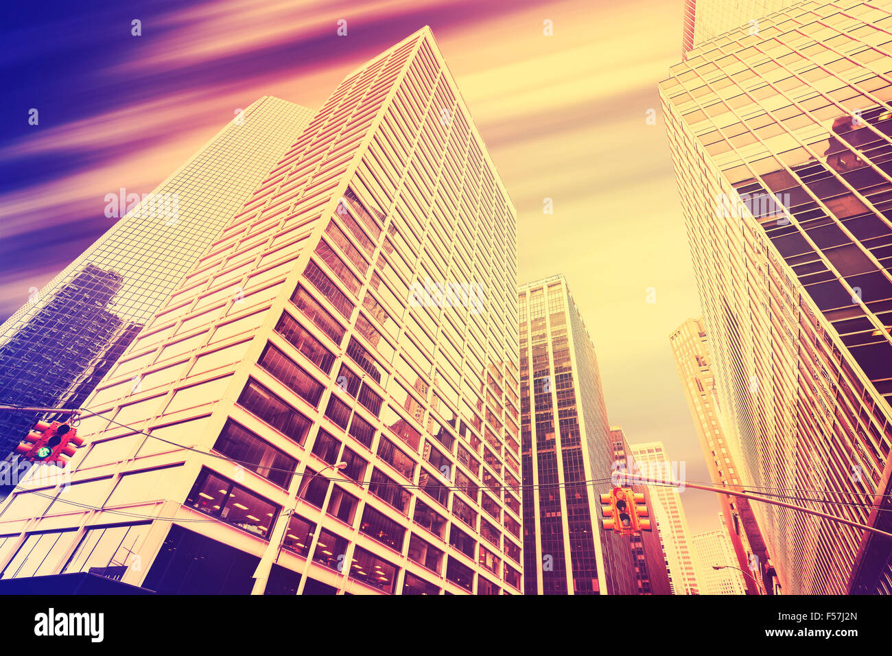 Vintage toned skyscrapers with motion blurred sky, modern business background. - Stock Image