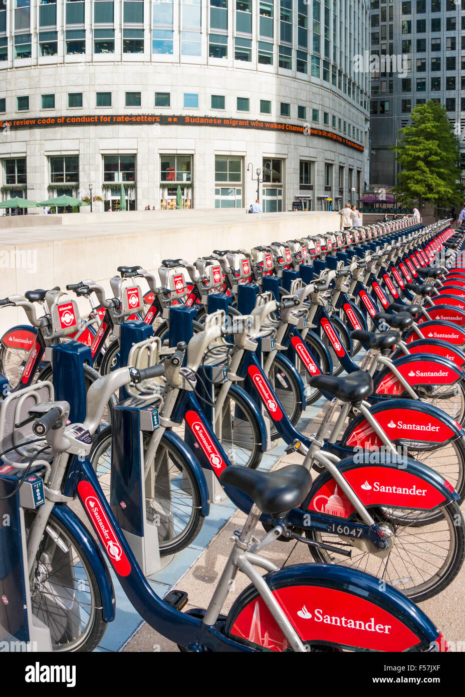 Santander red Boris Bikes for hire in a docking station Canary Wharf London England UK GB EU Europe - Stock Image