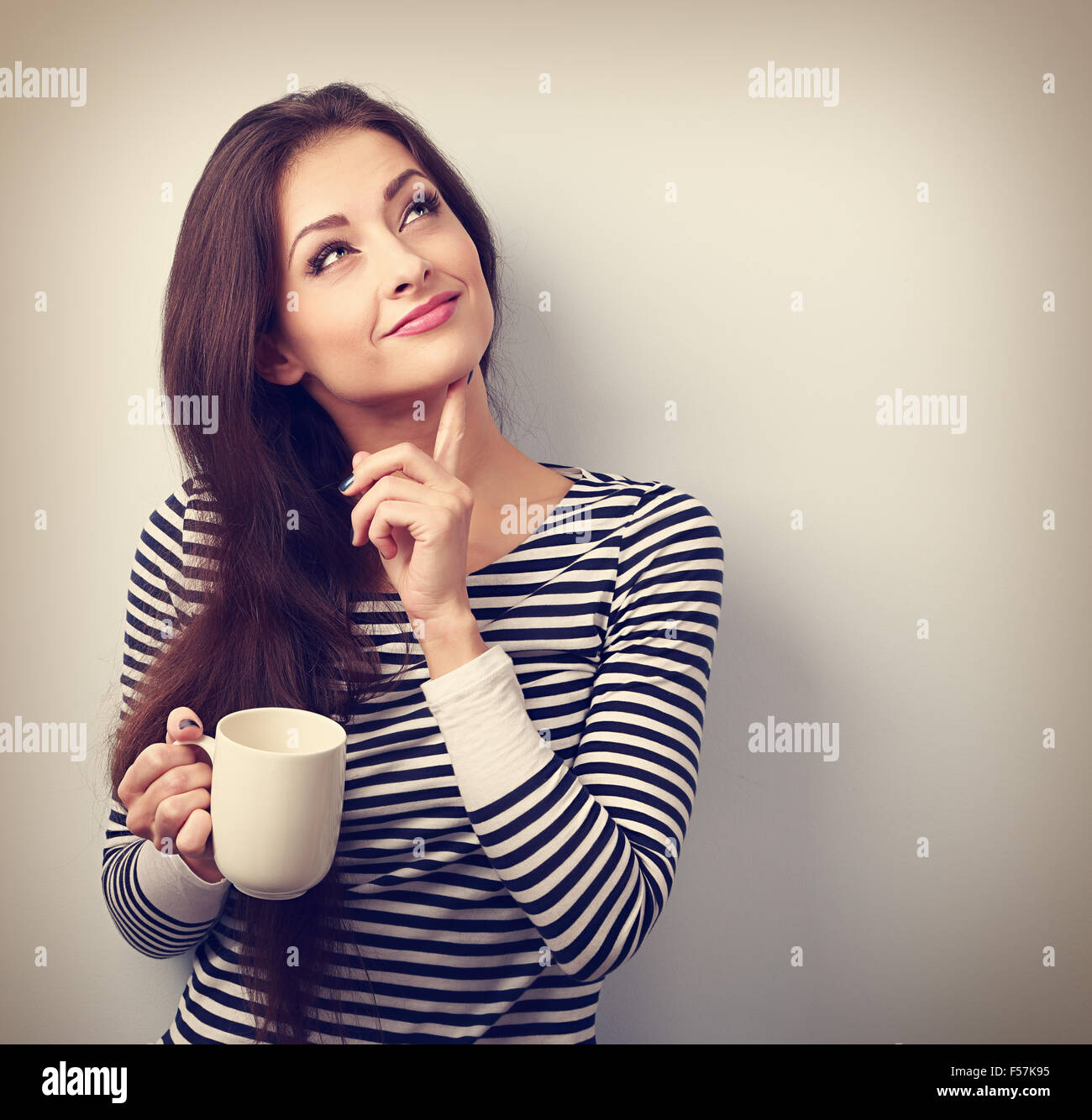 Thinking concerned young woman looking up with cup of coffee. Vintage portrait - Stock Image