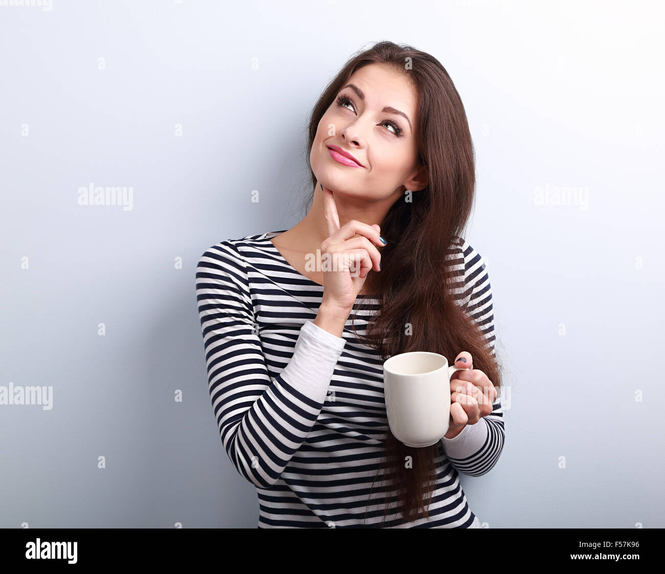 Thinking concerned young woman looking up with cup of coffee on blue background - Stock Image