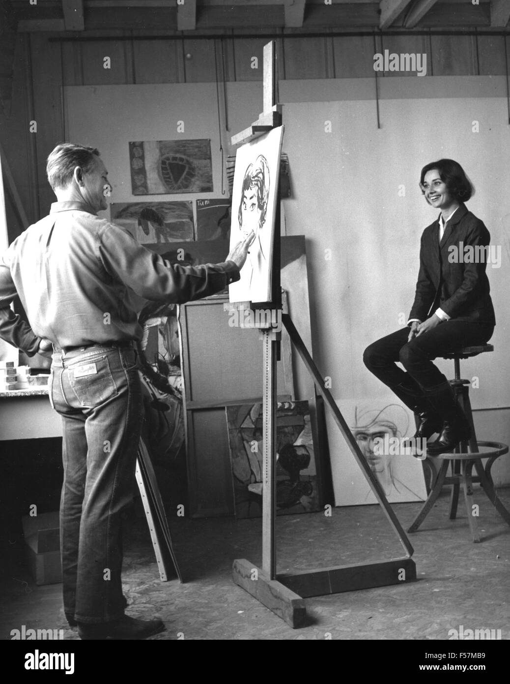 CHANNING PEAKE (1910-1989) American artist painting Audrey Hepburn about 1965 - Stock Image