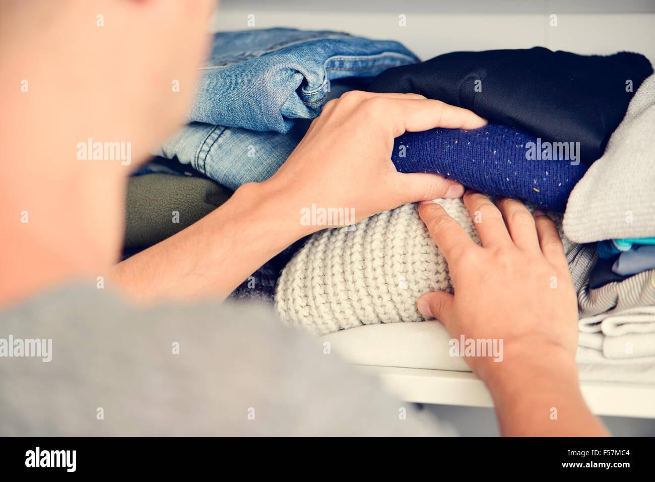 closeup of a young caucasian man arranging the closet - Stock Image