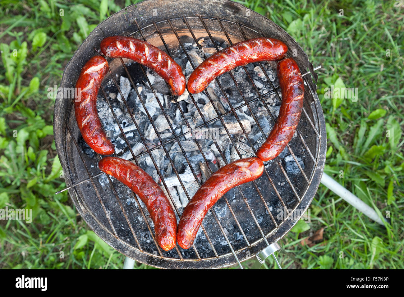 sausage on grill arranged in shape of heart - Stock Image