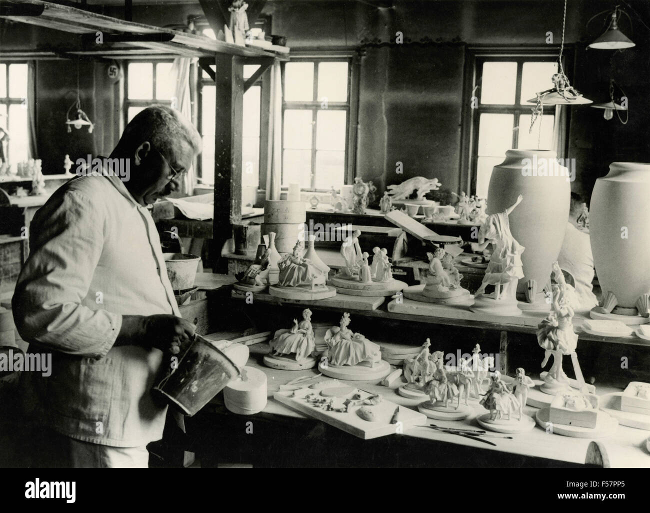 A man prepares porcelain figurines, Italy - Stock Image