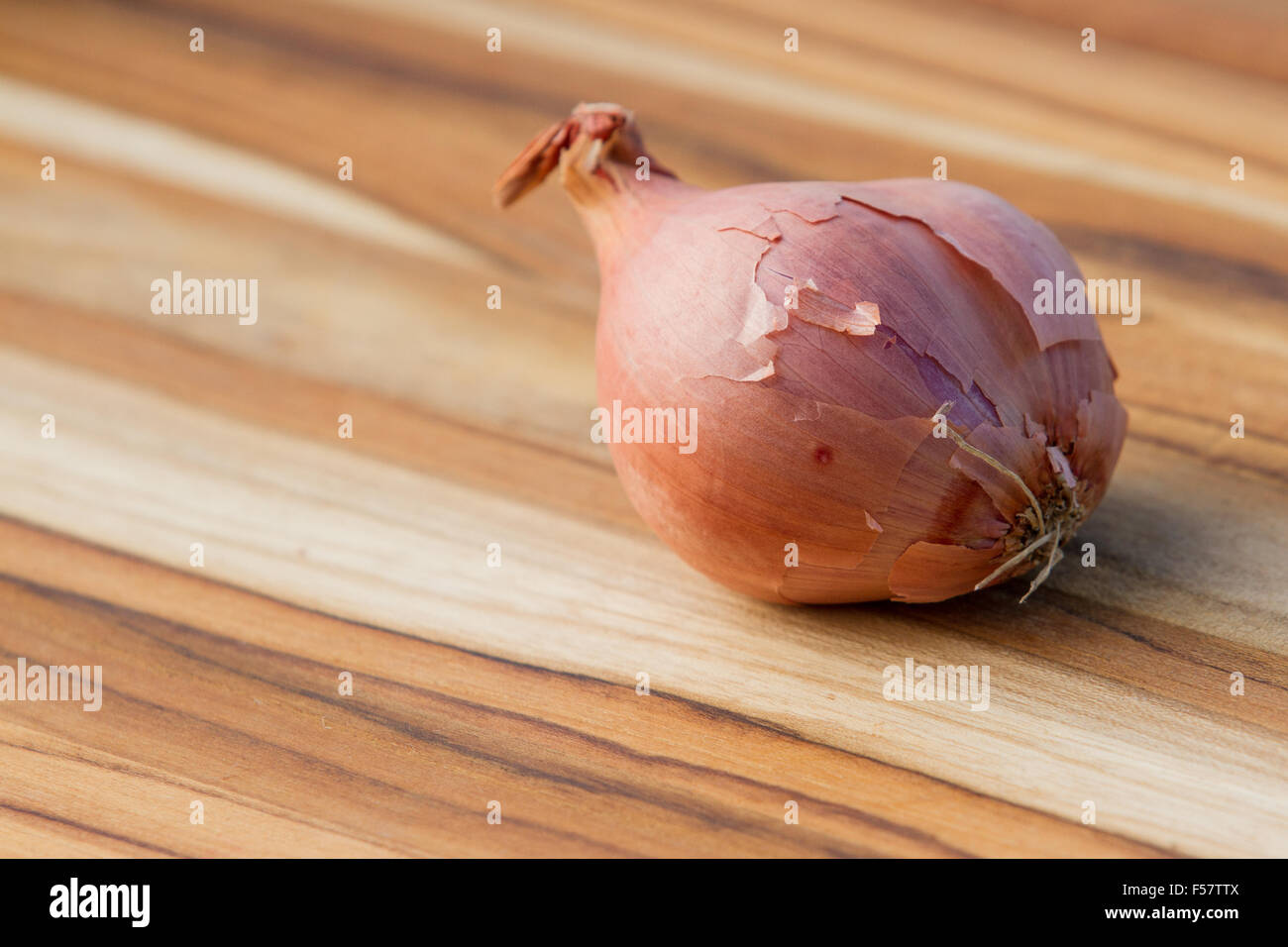 close up of an organic shallot on a wooden table - Stock Image