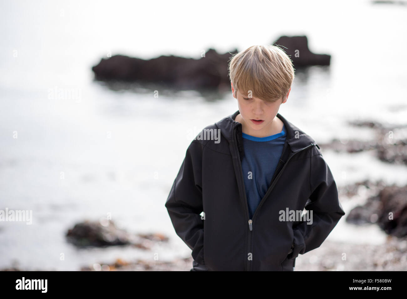 Fair-haired white teenage boy in a black jacket walks alone on a beach looking sad and unhappy in autumn sunshine - Stock Image
