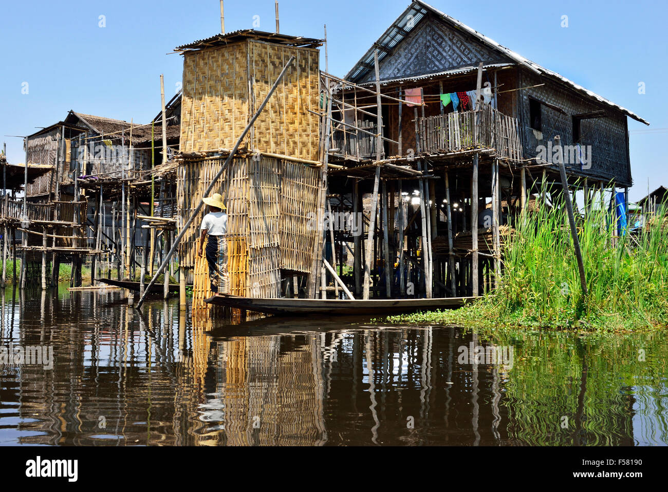 Ethnic minority Intha woman in small boat outside stilt house on Inle Lake,Shan State, Myanmar,(Burma) - Stock Image
