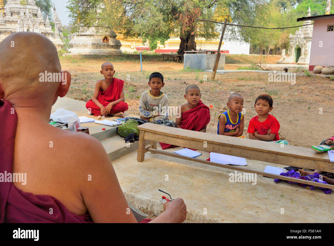 Buddhist Monk teaching schoolchildren lessons outdoors in the grounds of stupas and temples near Mandalay Myanmar - Stock Image