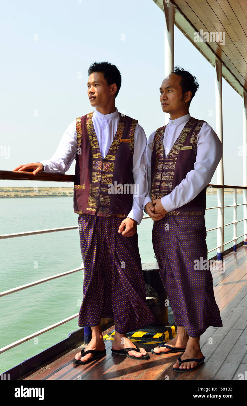 Two Burmese waiters on 'RV Paukan 2007 ' a traditional  Ayeyarwaddy River cruise  boat,looking out at the - Stock Image