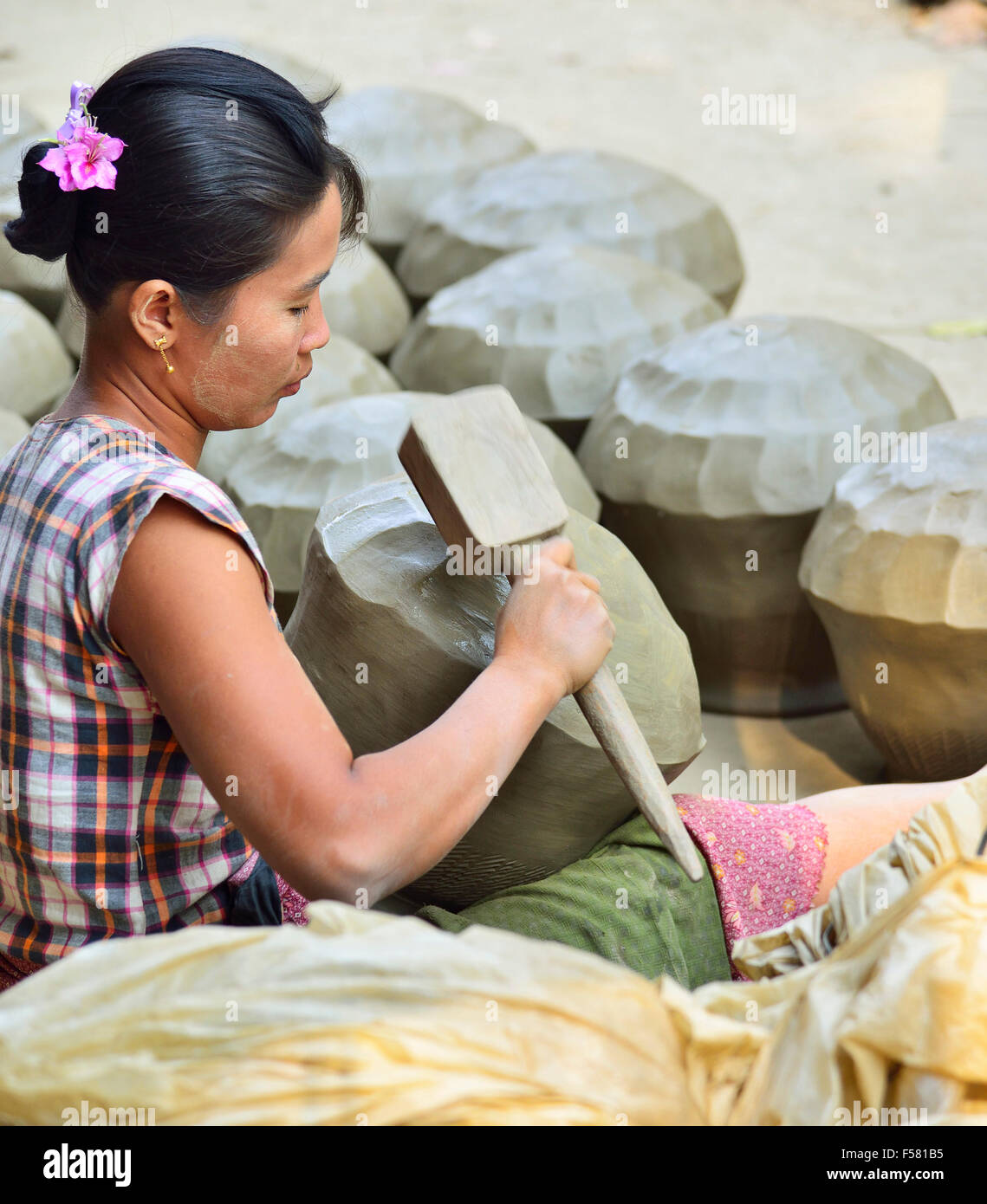 Woman in the irrawaddy village near Mandalay beating out  clay  water pots into shape with  a wooden paddle . - Stock Image