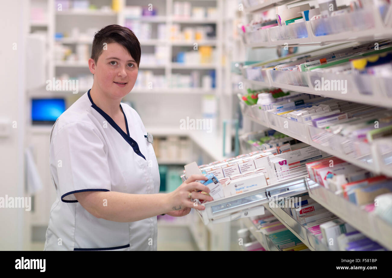 A female pharmacist at work in a chemist / pharmacy in South Wales, UK. - Stock Image