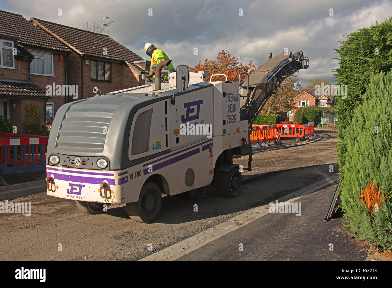 Road surface cutting machine driving down a road having skimmed off the top surface of Tarmac - Stock Image