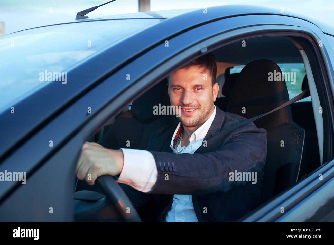 rent a car, smiling happy caucasian young man driving - Stock Image