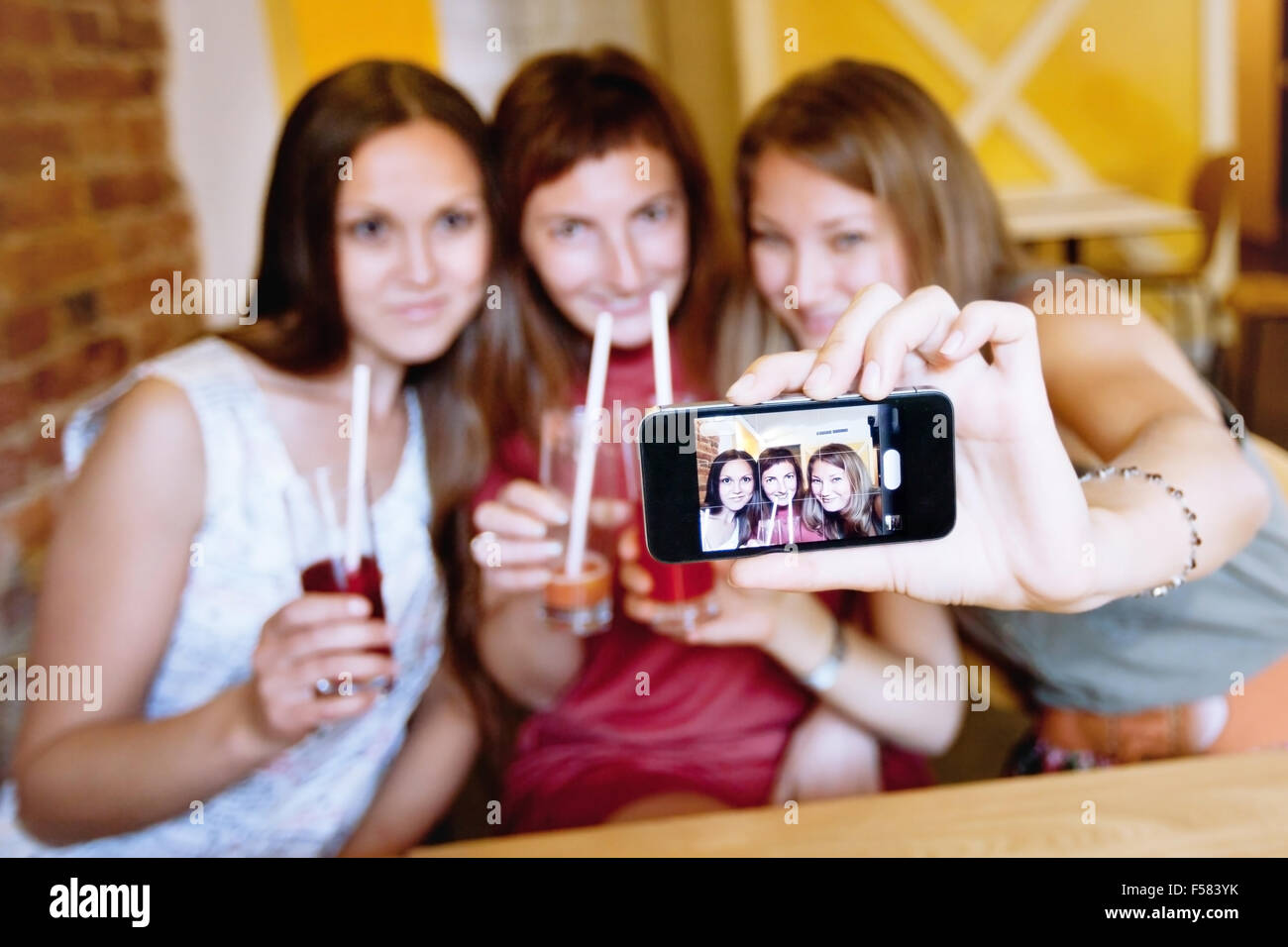 friends taking photo of themselves in cafe during party - Stock Image