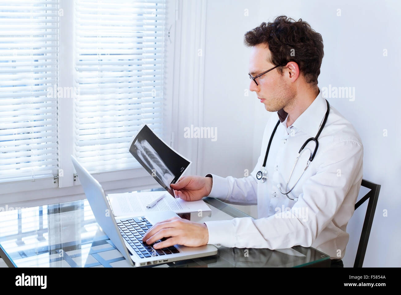 doctor in front of computer checking xray photo - Stock Image