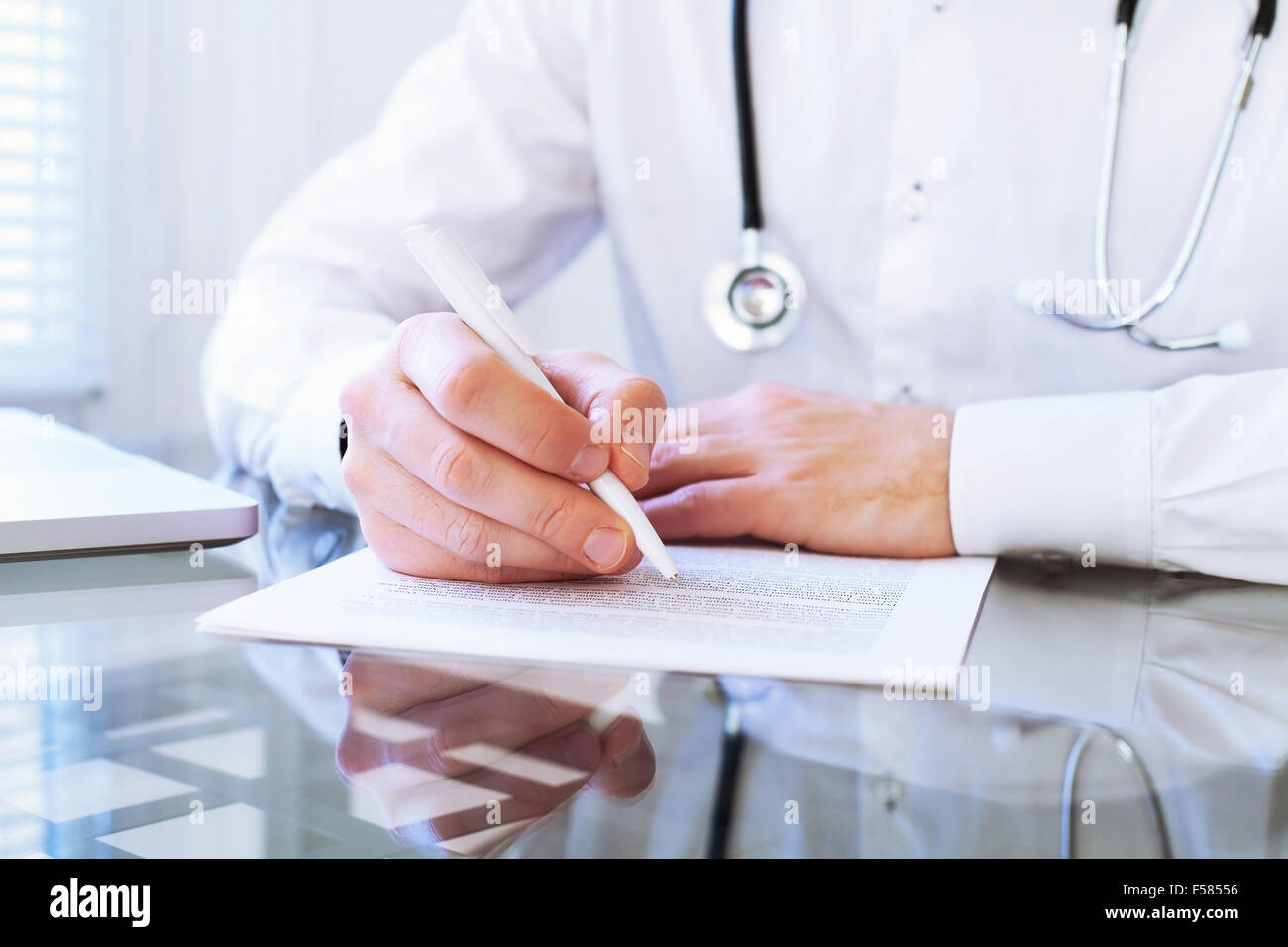 medical diagnose, hands of doctor writing in clinical record - Stock Image