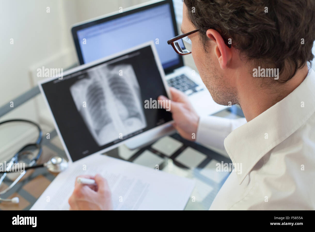 doctor looking at x-ray of lungs and writing diagnosis - Stock Image